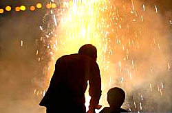 Father and son bursting crackers on Diwali
