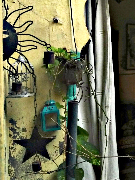 Potted plants and creepers soften the wrought iron of the wind chime while a bird cage and a lantern add whimsy.